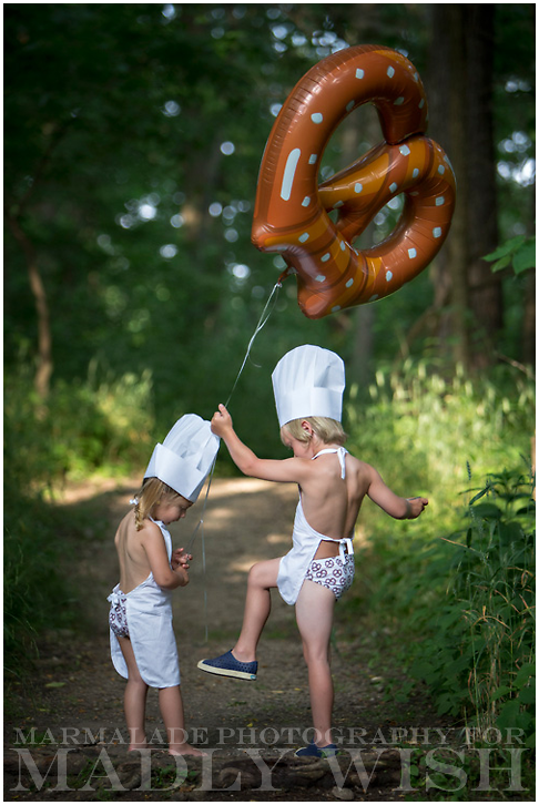 Photo of two children in the Chicago area playing in the forest surrounded by flying pretzels
