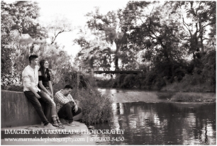 A photograph of older siblings: two brothers and their little sister overlooking a water way in the Chicago area.